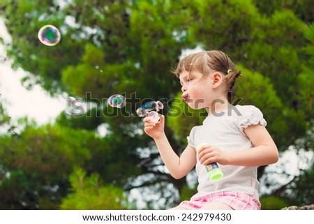 Girl blowing bubbles. lovely little girl blowing soap bubbles.