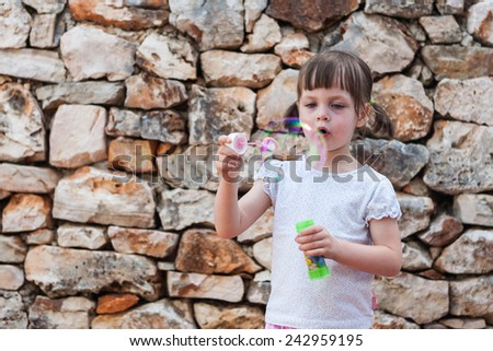 Girl blowing bubbles. lovely little girl blowing soap bubbles  - stones background
