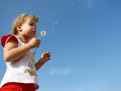 Girl blowing dandelion off