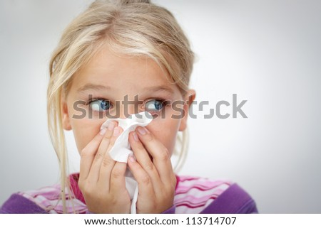 Girl blowing her nose. Space for text. Horizontal