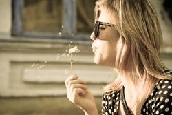 Girl blowing on a dandelion. Blowing of dandelion seeds.