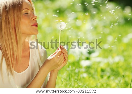 girl blowing on a dandelion lying on the grass #89211592