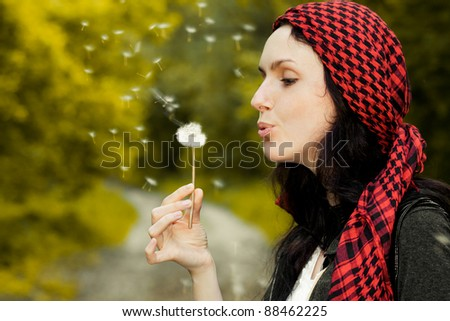 Girl blowing on white dandelion in the forest - stock photo