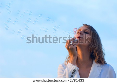 Girl blowing soap bubbles - stock photo