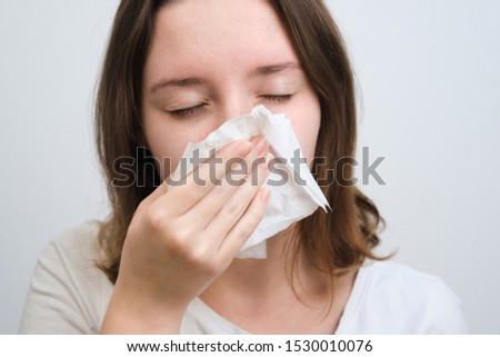 girl blows her nose in a handkerchief with a cold #1530010076