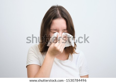 girl blows her nose in a handkerchief with a cold #1530784496