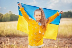 Girl blue and yellow flag of Ukraine in field. Ukraine's Independence Flag Day. Constitution day. 24 August. Patriotic holiday.