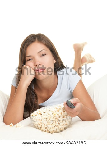 Girl bored watching boring movie in bed. Funny image of woman lying down in bed on White background eating popcorn and zapping changing channel on tv.