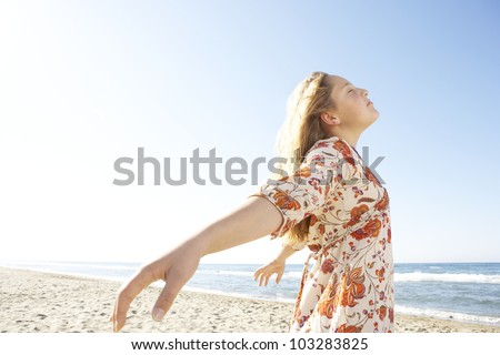 Girl breathing fresh air while standing by the shore on a white sand beach.