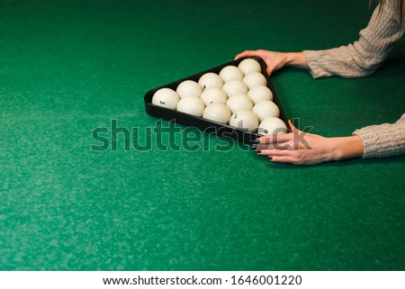 Girl builds a pyramid of balls in billiards. Woman playing in billiard