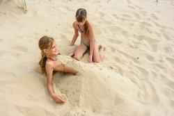 Girl bury her girlfriend with sand on the sandy beach