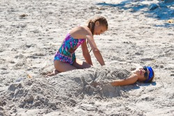 Girl burying boy in the sand. Children playing on the beach. Brother and sister playing together on the beach. Children's summer vacation. Life in the tropics