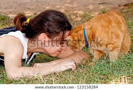 Girl butting heads with her ginger cat