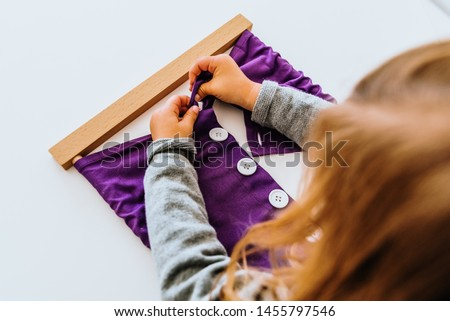 Girl buttoning a montessori frame to develop the dexterity of her fingers. #1455797546