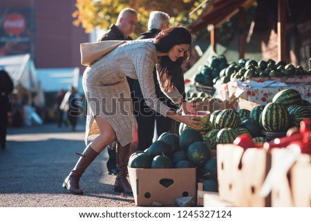 Girl buys healthy melon and other fresh vegetables and fruits from local farmer market. Bio natural ingredients cooking farm to table organic concept