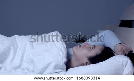 Girl can not fall asleep. Insomnia noisy neighbors concept. Young attractive caucasian girl lies alone in bed under covers and looks at ceiling. Medium shot