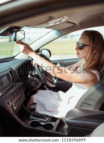 girl car, looks rearview mirror, parks parking lot of shopping center, holds fastened behind wheel. Woman summer sunglasses city wearing pink dress. Checks children back row seats. Happy smiles