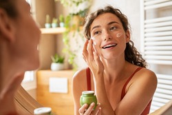 Girl caring of her beautiful skin face standing near mirror in the bathroom. Young woman applying moisturizing cream on face. Smiling natural girl holding little green jar of ecological cosmetic cream