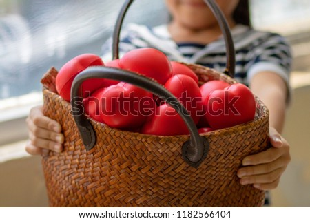 Girl carries the wicker basket full of red heart massage balls. she send them to someone she love.