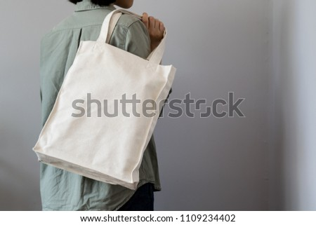 girl carrying totebag on gray background