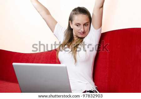 Girl celebrates in front of her laptop. Shot on red couch at living room