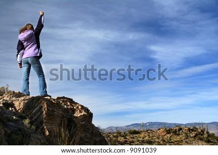 Girl celebrating victory after climbing a rock. Saguaro National Park, Arizona