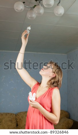 Girl changes light bulb at her home