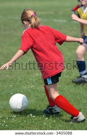 Girl Chasing Ball at Soccer Game - stock photo
