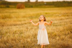 girl chasing soap bubbles on the sloping wheat field at sunset in village
