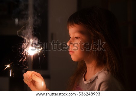 Stock Photo girl, child holds in his hands a Sparkler on a dark background at home