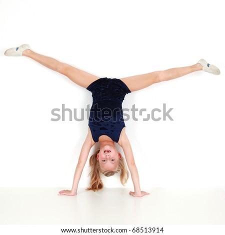 Girl child performing gymnastic balance training on white background
