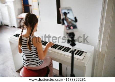 Girl child plays the digital piano and records video on the phone, online learning and video chat on learning to play the piano, remote music lessons online. Authentic lifestyle in a real interior