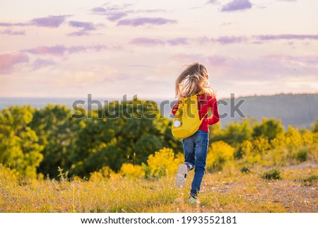 Girl child running in the evening with a backpack in nature on the background of a flowering meadow, steppe, active healthy lifestyle