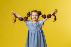 Girl child shows very long healthy braids. Children's hairstyle original ponytails. Barber hairdresser. Hair Care Shampoo concept. Hair band styling. Yellow background place for text banner. Funny kid