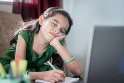 Girl child sleeping during online class infront of laptop - concept of tired kid from distance learning or online education at home during covid-19 or coronavirus lockdown