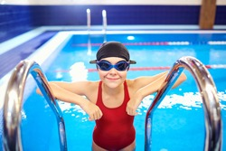 Girl child swimmer in a red bathing suit on a background of the pool inside the room with glasses and a cap.