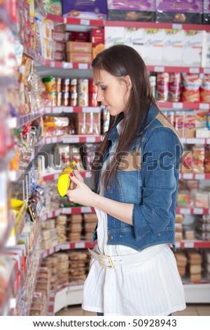 Girl choose food in supermarket