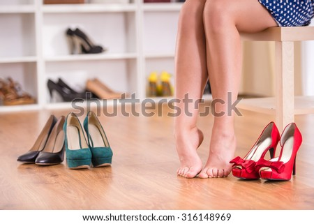 Girl chooses shoes in wardrobe room, more shoes lying in a row near her.