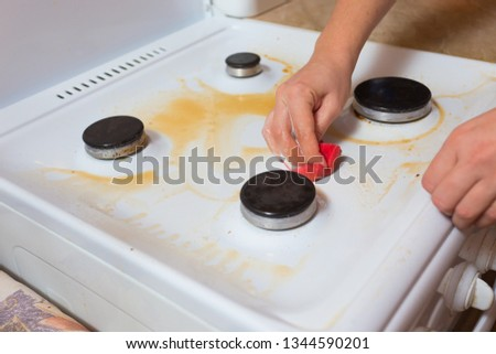 Girl cleans the kitchen, cleans the surface of the gas stove #1344590201