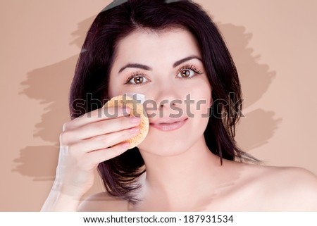 Girl cleans the skin cream with a sponge (unusual toning )
