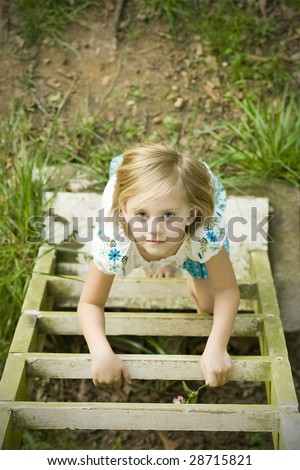 Girl climbing ladder into tree house