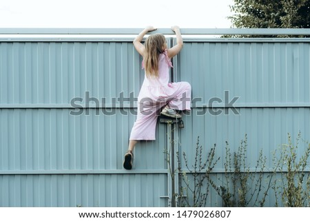 Girl climbing metal fence outdoor. Curious child on high white painted gates. Naughty kid playing outside, breaking rules. Childhood and youth concept. Restless teen entering private property #1479026807
