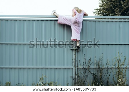 Photo of  Girl climbing metal fence outdoor. Curious child on high white painted gates. Naughty kid playing outside, breaking rules. Childhood and youth concept. Restless teen entering private property