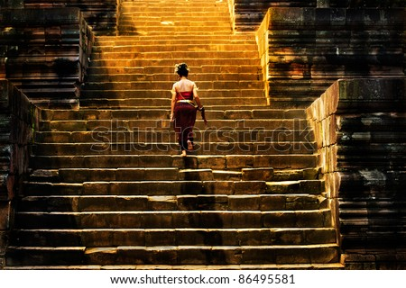 girl climbing up stairs of castle stone - stock photo