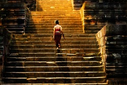 Girl climbing up stairs of castle stone. She walking slow step, go to the big door. The sun is shining to the stairs in the morning. All wall is make by stone. It is ancient building style.
