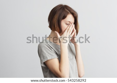 Girl closes in frustration her face. To be ill with influenza and the common cold. Forget and remember something, suffer from illness.