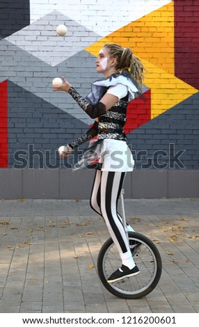Girl clown rides a unicycle and juggles balls  in front of colorful wall outdoors