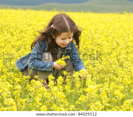 Girl collecting flowers in a yellow blooming field