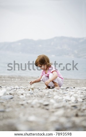 girl collecting stones on the beach