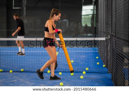 Girl collects padle or tennis balls in the middle of the court Stock fotó ©